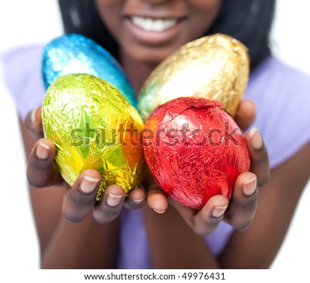 Close-up of a woman showing colorful Easter eggs against a white background - stock photo