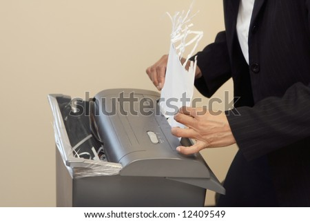 Close-up of a woman shredding a piece of paper in an office shredder - stock photo