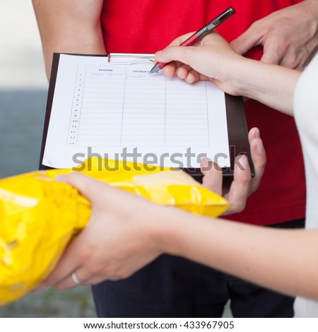 Close-up of a woman signing document of delivered package - stock photo