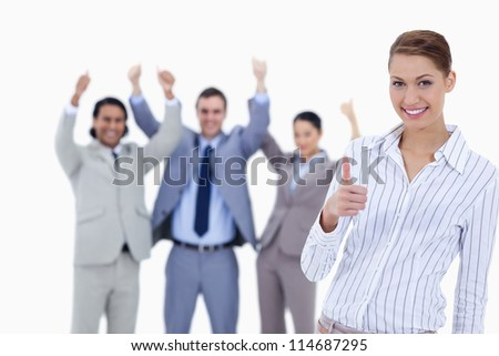 Close-up of a woman smiling and approving with enthusiastic business people with their thumbs up in background - stock photo