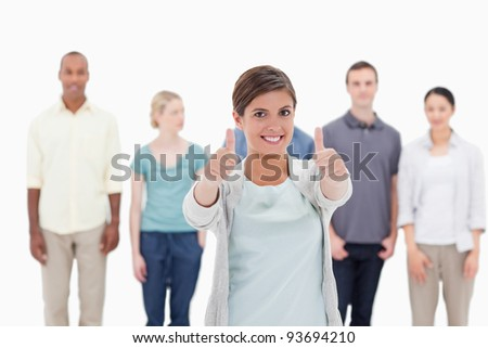 Close-up of a woman smiling giving the thumbs-up with people behind against white background - stock photo