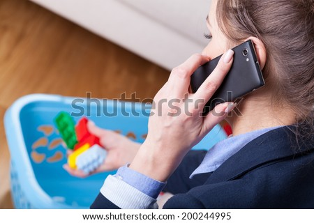 Close-up of a woman talking on phone and cleaning up kids toys - stock photo