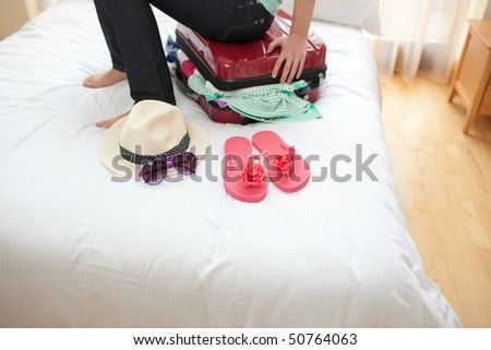 Close-up of a woman trying to close her suitcase on her bed - stock photo