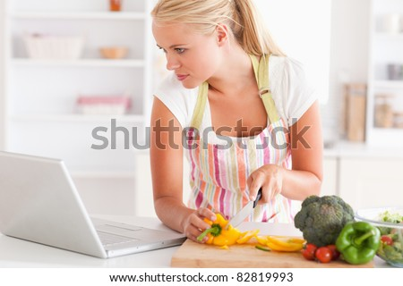 Close up of a woman using a laptop to cook in her kitchen - stock photo