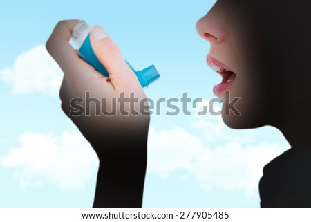 Close up of a woman using an asthma inhaler against blue sky - stock photo