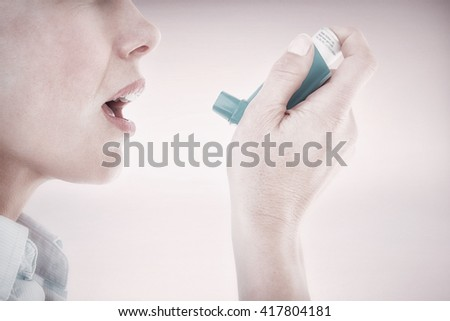 Close up of a woman using an asthma inhaler against grey background - stock photo