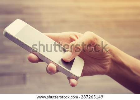 Close up of a woman using mobile smart phone,in vintage style - stock photo