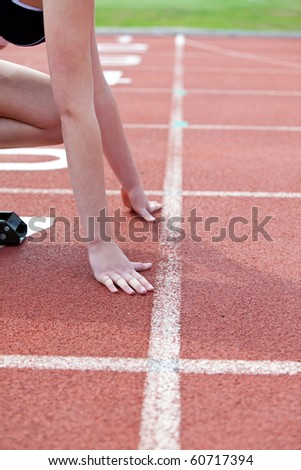 Close-up of a woman waiting in starting block in a stadium - stock photo