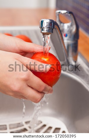 Close-up Of A Woman Washing Tomato In Running Water Under Tap - stock photo