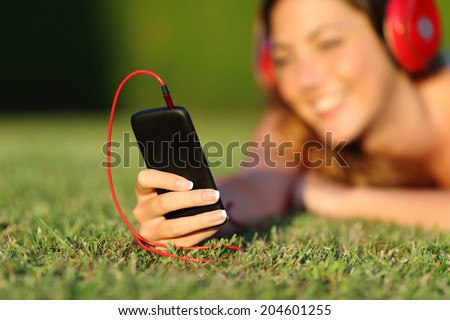 Close up of a woman with headphones holding a smart phone lying on the grass in a park or a garden           - stock photo