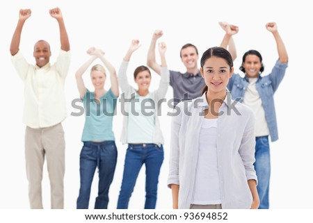 Close-up of a woman with people raising their arms in background - stock photo