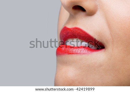 Close up of a womans face with bright red lipstick biting her lips. - stock photo