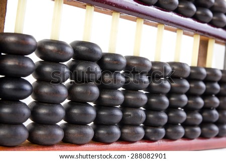 Close up of a wooden abacus beads. Selective focus, shallow depth of field. Wooden abacus on white background. - stock photo