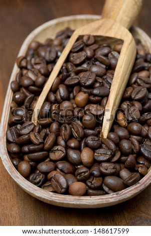 close-up of a wooden bowl with coffee beans, vertical