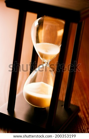 Close up of a wooden hourglass with running sand and glass bulb measuring the passing time to a deadline or end point - stock photo