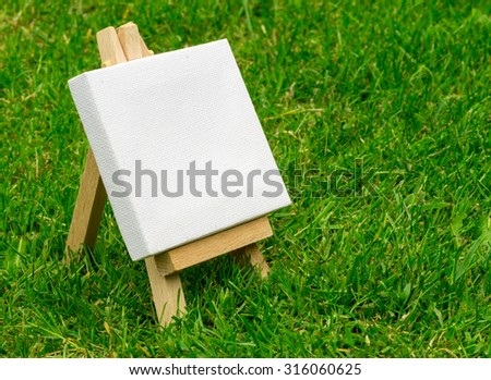 Close up of a wooden miniature model artists easel on grass with copyspace area and design space