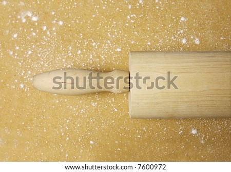 Close-up of a wooden rolling pin on flattened dough - stock photo