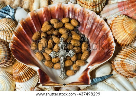 Close up of a wooden rosary beads with a silver crucifix in a scallop seashell. Symbol of Christian pilgrimage - stock photo