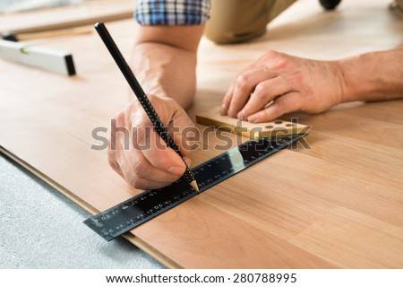 Close-up Of A Worker Drawing A Mark On Laminate Using Ruler - stock photo
