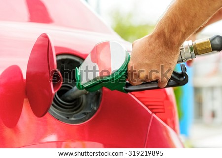 Close up of a worker hand, loading gas into car. Gas station. - stock photo