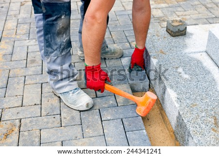 Close up of a worker places paving stones in front of a private house, using a rubber hammer for fixing the stones. - stock photo