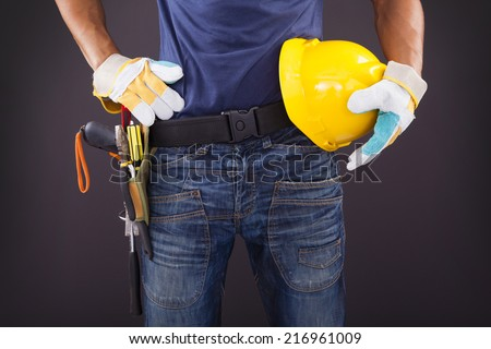 Close up of a worker with toolbelt and helmet against black background - stock photo