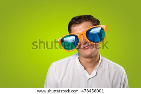 Close up of a worried guy with a large glasses on green background