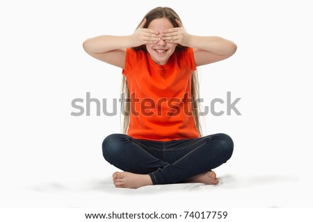 close-up of a 10 year old girl with hands covering eyes playing hide and seek