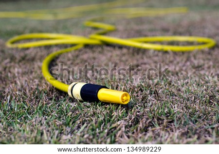 Close up of a yellow gardening water pipe lying and dripping a drops of water to dry grass during hot summer. - stock photo