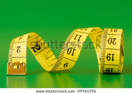 close-up of a yellow measure tape,isolated on green background - stock photo