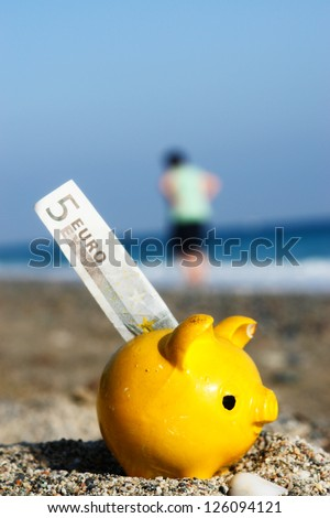 close up of a yellow piggybank on the beach - stock photo