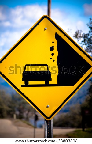 Close-up of a yellow sign with a car silhouette and falling rocks - stock photo