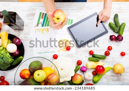 Close-up of a young adult woman informing herself with a tablet PC about nutritional values of fruits and vegetables.  - stock photo