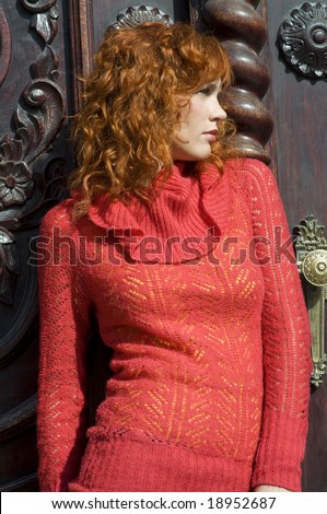 close up of a young and beautiful woman with red pullover near old door