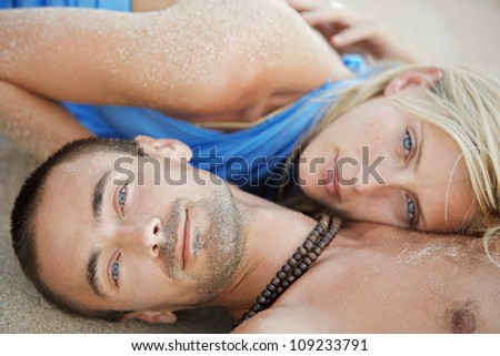 Close up of a young attractive couple laying down on golden sand, relaxing on the beach.