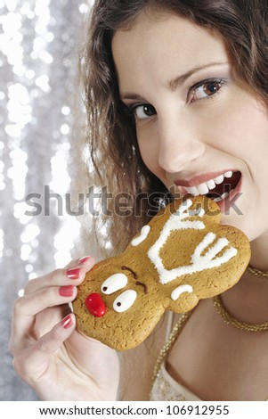 Close up of a young attractive woman biting a Christmas decorated buiscuit. - stock photo