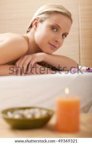 Close-up of a young beautiful woman at spa, focus on background - stock photo