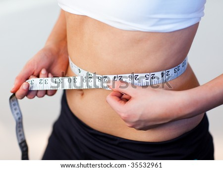 Close-up of a young beautiful woman measuring her waist with an tape measure - stock photo