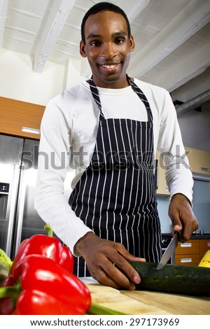 close up of a young black man wearing an apron and cooking at home. he is in a domestic kitchen and preparing a vegetarian meal. - stock photo
