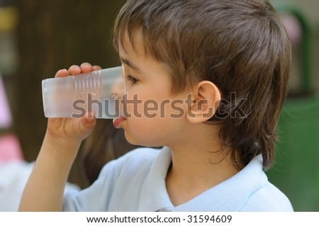 Close up of a young boy drinkin cup of water