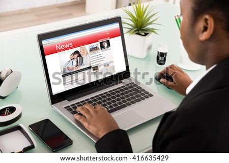 Close-up Of A Young Businesswoman Reading News On Laptop - stock photo