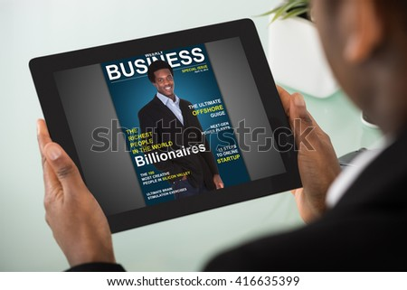 Close-up Of A Young Businesswoman Reading Online Magazine On Digital Tablet - stock photo