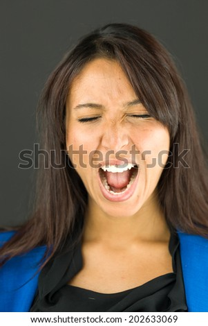 Close up of a young businesswoman shouting in excitement - stock photo
