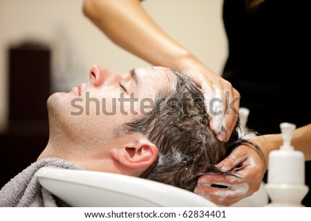 Close-up of a young caucasian man having his hair washed in a hairdressing salon - stock photo