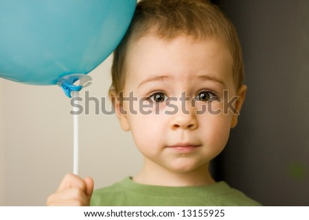 Close-up of a young child holding a blue balloon