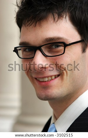 Close-up of a young corporate male worker smiling. - stock photo