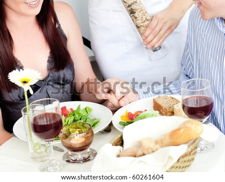 Close-up of a young couple dining at the restaurant with waiter putting pepper in their plate - stock photo