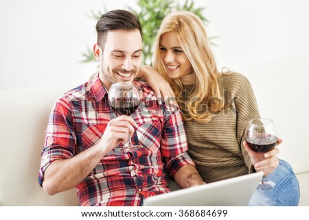 Close up of a young couple enjoying wine at home.They are sitting close to each other and drinking red wine.Love. - stock photo