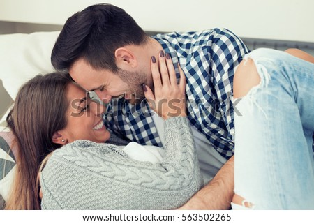 Close up of a young couple in love at home.They are sitting close to each other and enjoying together.