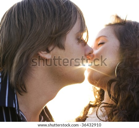 Close-up of a young couple kissing each other in the light of sunset - stock photo